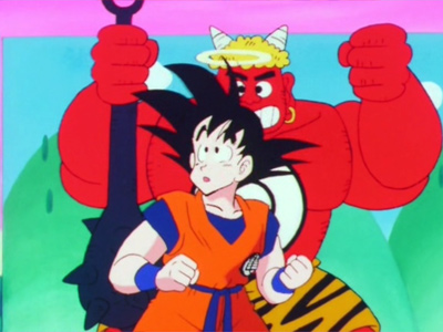 Goku stands in front of a traditional looking Oni cardboard cut out.  From DBZ episode 13.