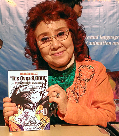 Masako Nozawa holds a signed copy of 'It's Over 9,000!'